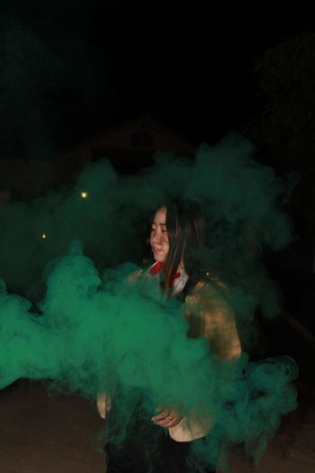 Young woman with distress flare standing against sky at night