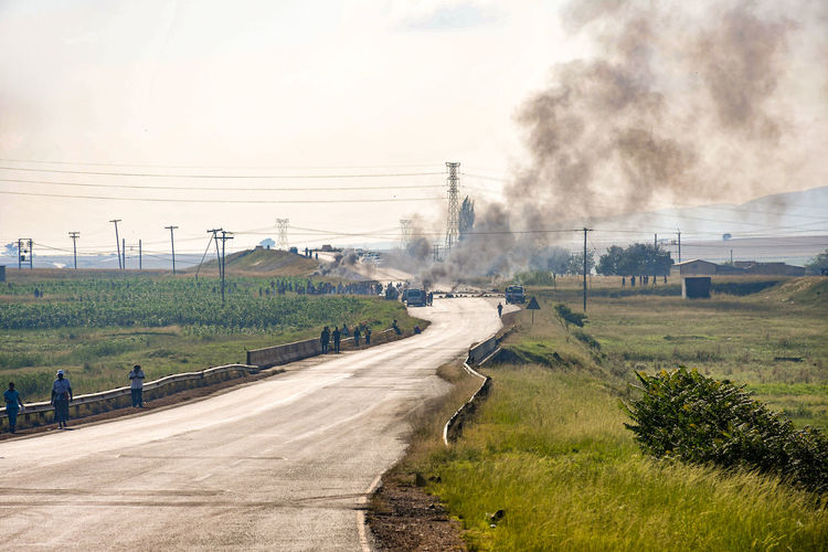 Protesters blocking the road with burning tyres. Pollution Protesters Rural Smoke Day Countryside Colors Sunny Motion Hill Trip Journey Wind House Activity Action Car Environment People Vehicle Street Streetphotography Grass Outdoors Outdoor Photography Field Road Travel Tree Sky The Photojournalist - 2019 EyeEm Awards The Street Photographer - 2019 EyeEm Awards