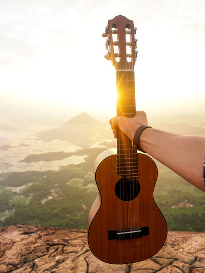 Cropped hand of man holding guitar on mountain against sky during sunset