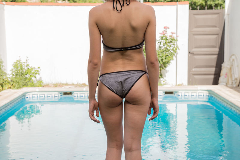 Midsection rear view of bikini woman standing by swimming pool against sky