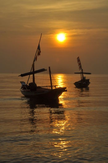 Two Boats On Sea Against Sky During Sunset