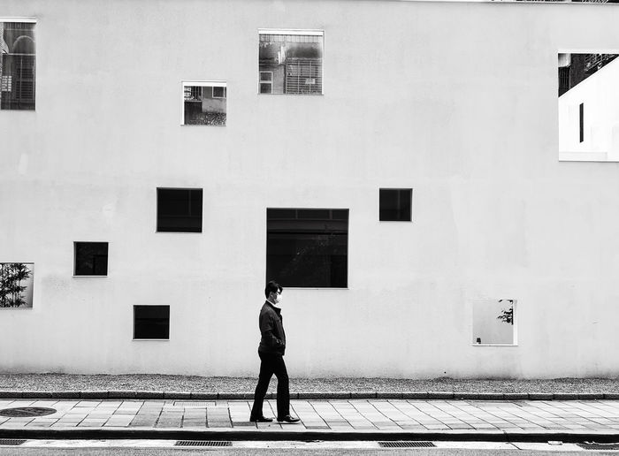Side view of man walking by building in city