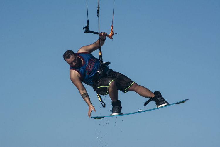 Low angle view of man kiteboarding against clear sky
