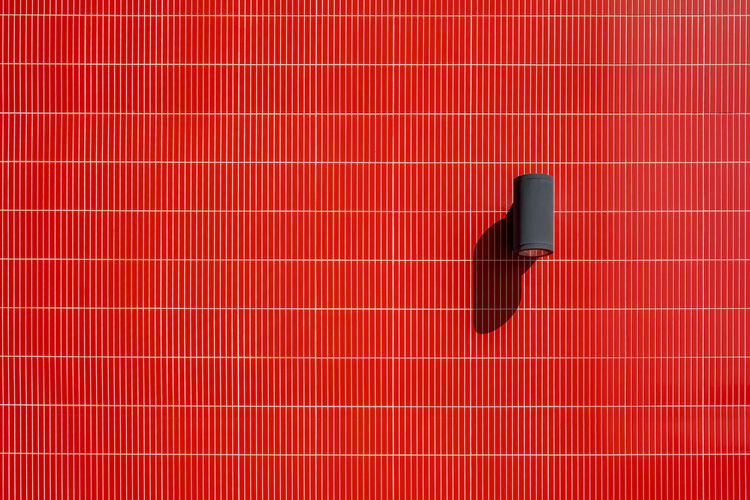 Industrial design outdoor spotlight lamp on vivid red tiled wall with copy space