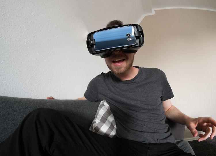 3f61b0e2792 Male with beard sitting on a couch enjoying a virtual reality experience  Glasses Goggles Virtual Reality
