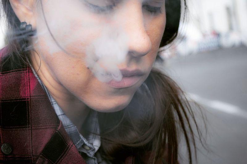 Close-up of young woman exhaling smoke