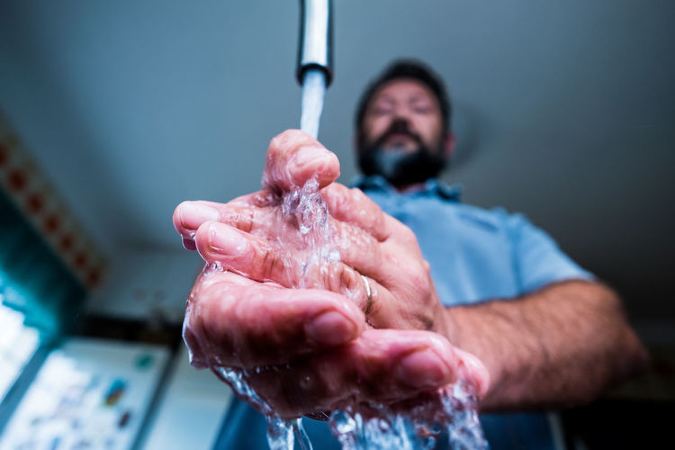 Low angle view of man washing hands at home