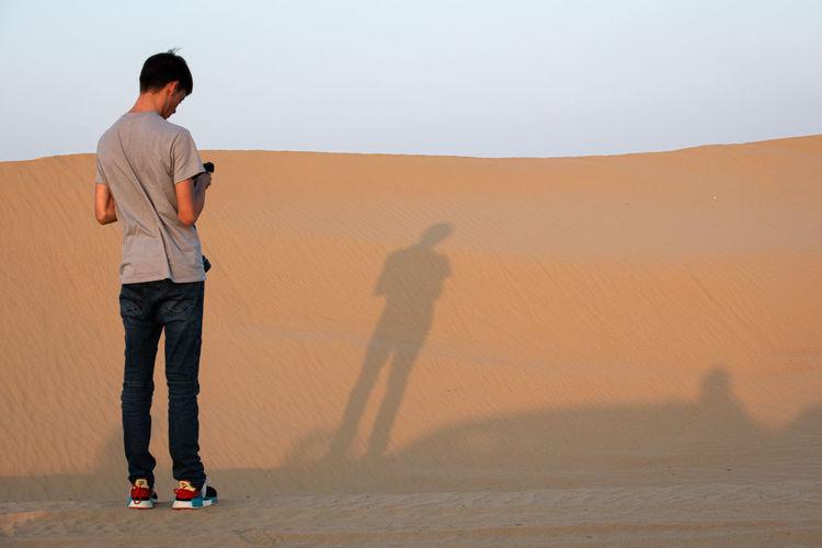 Men standing on sand dune in desert against sky
