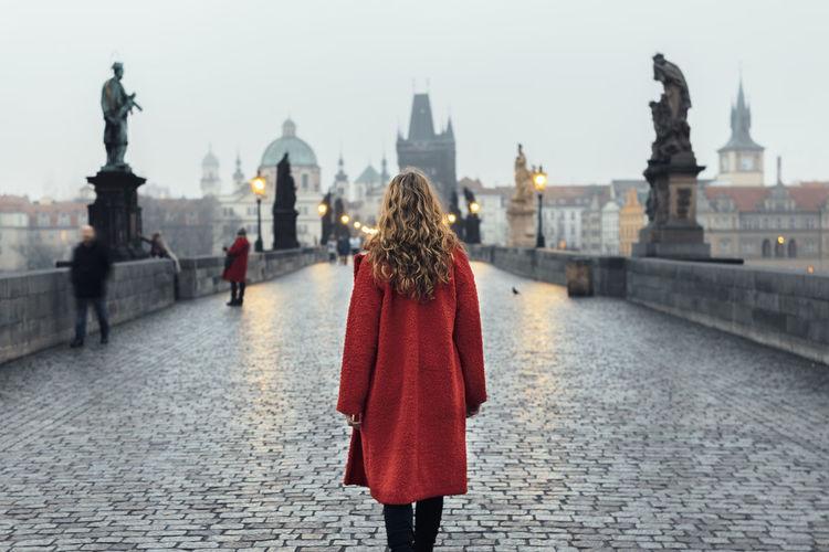 Rear view of woman walking on bridge by street lights at sunrise