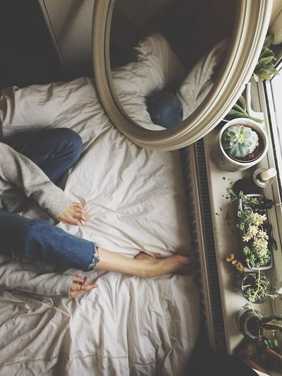 High angle view of girl sitting on bed
