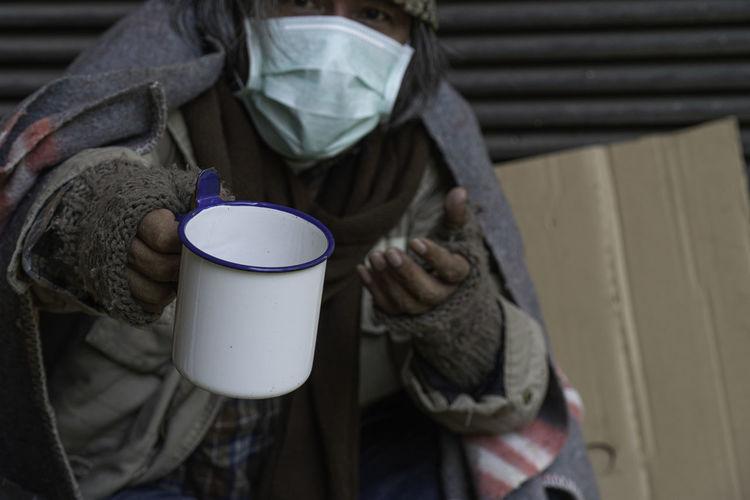 Beggar holding mug while begging