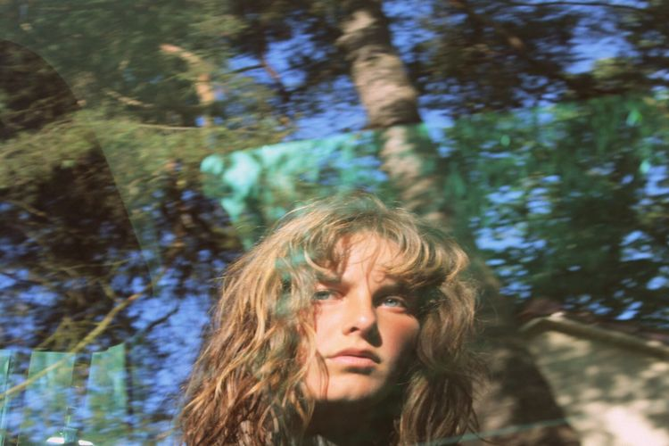 Portrait of young woman against tree trunk reflecting on window