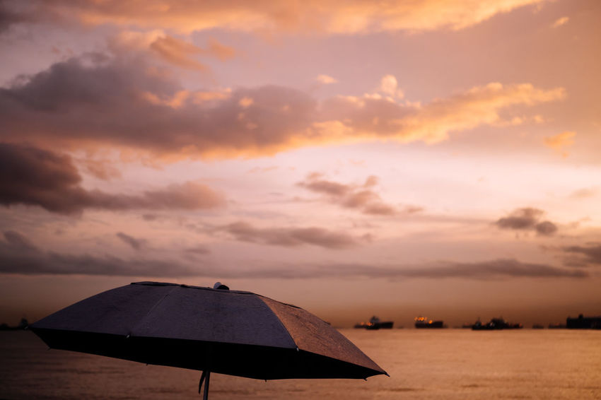 Umbrella in rain under warm-colored sky in front of sea Sky Cloud - Sky Sunset Scenics - Nature Beauty In Nature Nature Orange Color Tranquil Scene Environment Outdoors Umbrella No People Sea Water Rain Evening Morning Warm Colors Tranquility