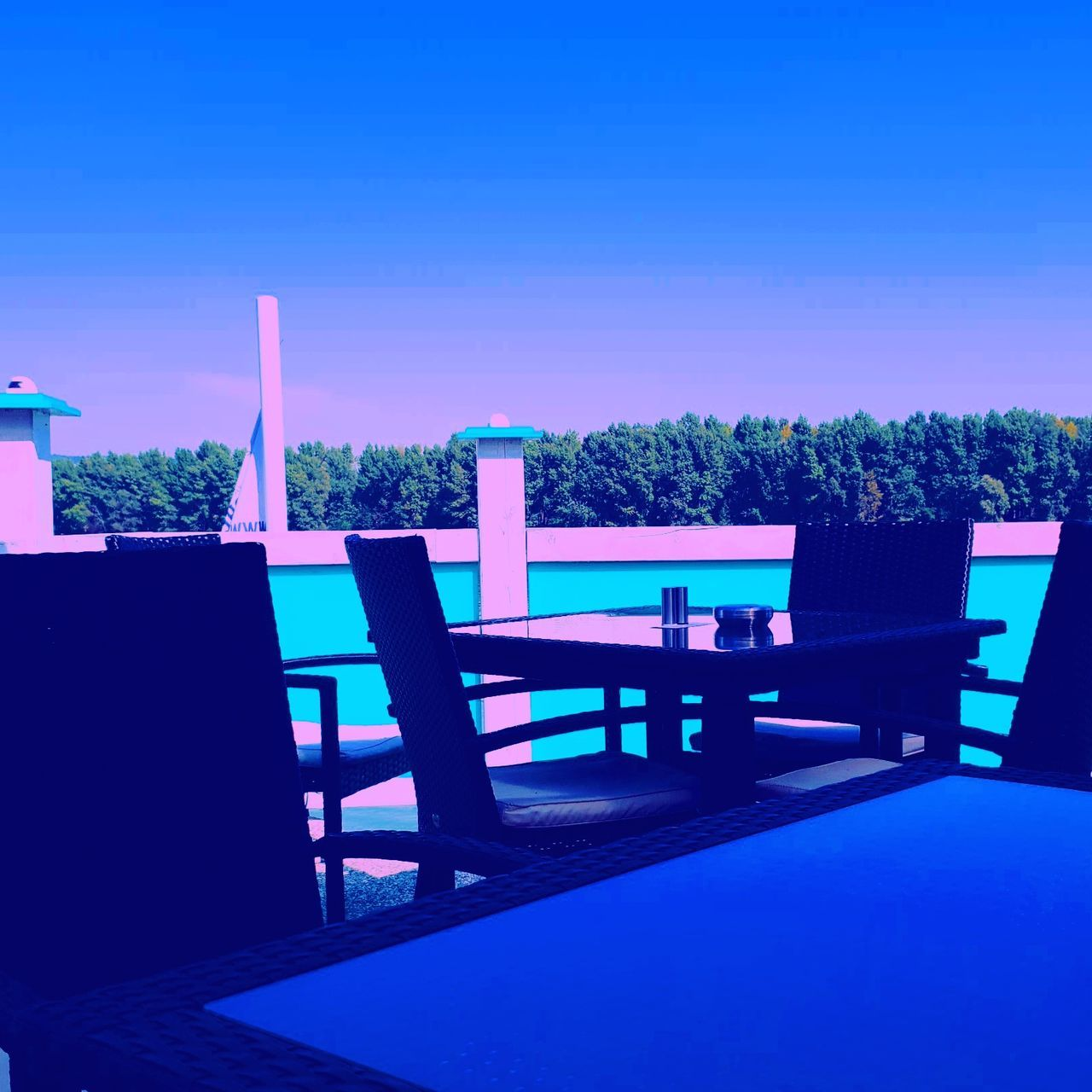 EMPTY CHAIRS AND TABLES AGAINST CLEAR BLUE SKY