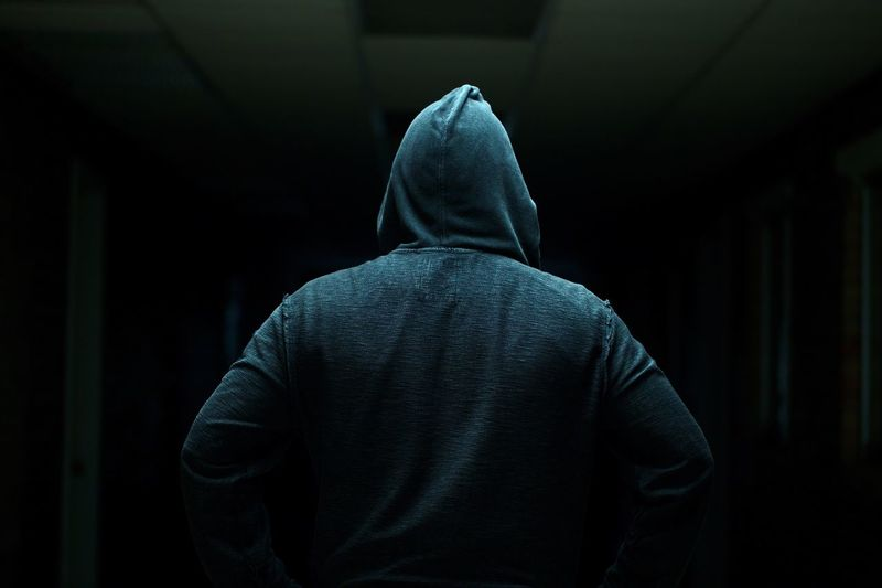 Rear view of man standing against black background