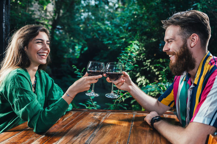 Couple Toasting With Red Wine On A Date Romantic Dinner Couple Red Wine Toasting Toasting Glasses Date Relationship Dating Restaurant Happiness Romance Anniversary Green Alcohol Two People Young Dinner Lunch Smiling Table Young Women Emotion Couple - Relationship Positive Emotion Celebratory Toast