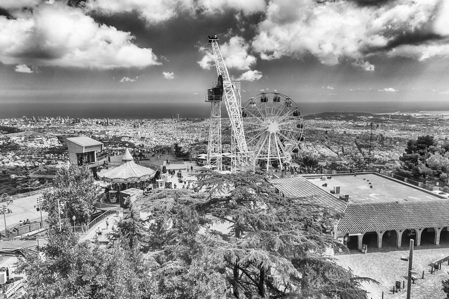 BARCELONA - AUGUST 12: View over the Tibidabo Amusement Park and Barcelona, Catalonia, Spain on August 12, 2017. The park opened in 1905 and is among the oldest in the world still functioning Architecture Built Structure Building Exterior Sky Cloud - Sky High Angle View Nature Tree City Building Day Plant No People Cityscape Outdoors Residential District Travel Destinations Water Travel