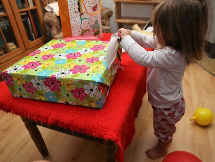 Full length of cute girl opening gift at home