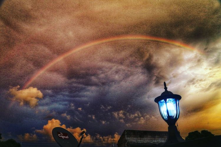 Low angle view of street light against rainbow