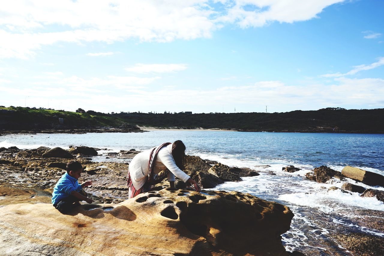 real people, sitting, sky, water, rock - object, cloud - sky, nature, day, togetherness, leisure activity, sunlight, beauty in nature, men, outdoors, boys, scenics, lake, two people, full length, women, mammal