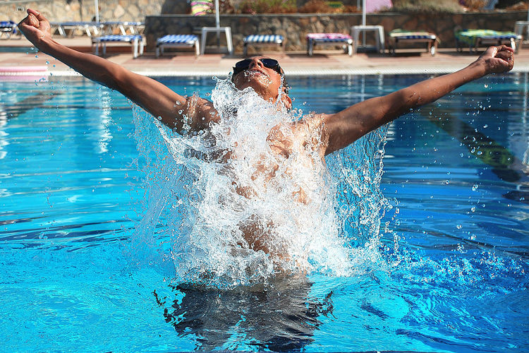 Man with arms outstretched splashing water in swimming pool