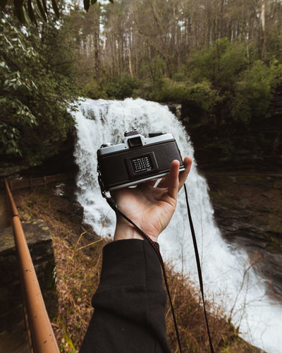 Cropped hand of person holding camera against waterfall