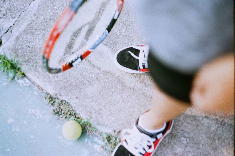 Close-up of person holding tennis racket
