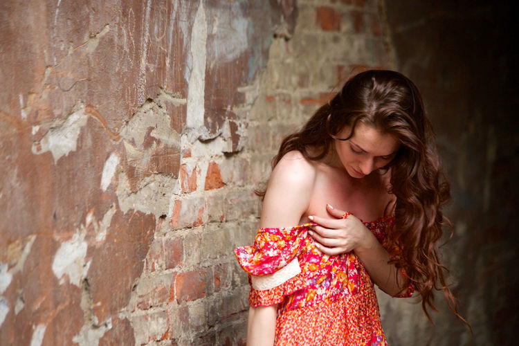 Beautiful girl in red dress Adult Beautiful Woman Beauty Brick Brown Hair Contemplation Depression - Sadness Emotion Hair Hairstyle Long Hair Looking Looking Down One Person Red Standing Teenager Wall Wall - Building Feature Women Young Adult