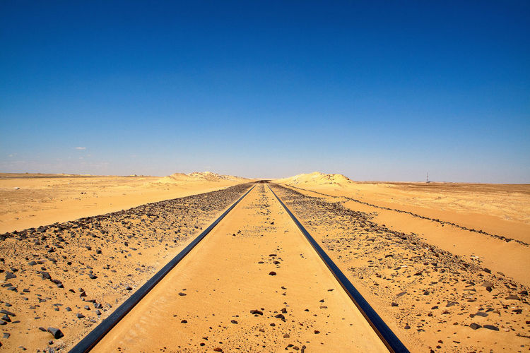 Road at desert against clear sky