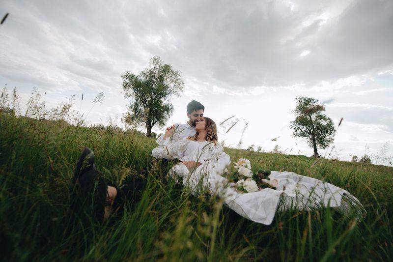 Happy Wedding Couple Sitting On Grassy Field Against Sky