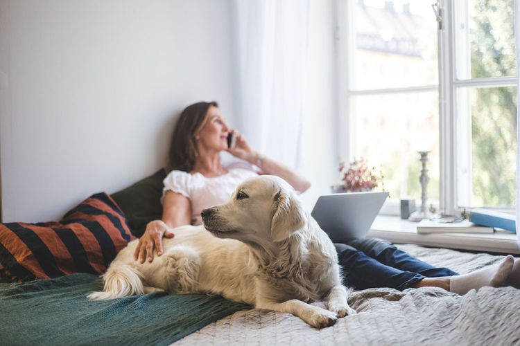 Woman with dog sitting on window at home