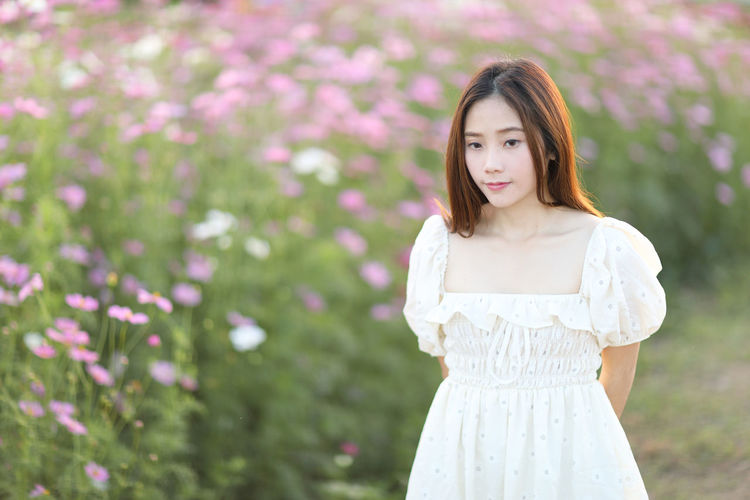 Portrait of a beautiful young woman standing by white flower