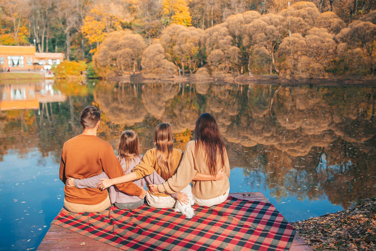 Group of people sitting on rock with reflection in water