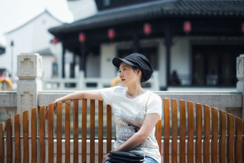 Woman looking away while sitting on bench