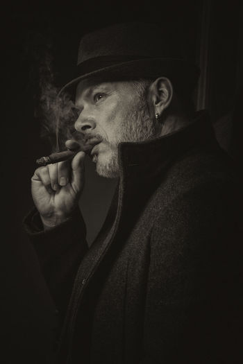 Model: Michael Wipperfürth Bild 3 von 3 Old-fashioned Addiction Adult Bad Habit Black Background Bnw Black And White Cigar Hat Headshot Indoors  Lifestyles Men Menstyle Night One Men Only One Person Only Men People Portrait Real People Retro Styled Smoke - Physical Structure Smoking - Activity Smoking Issues