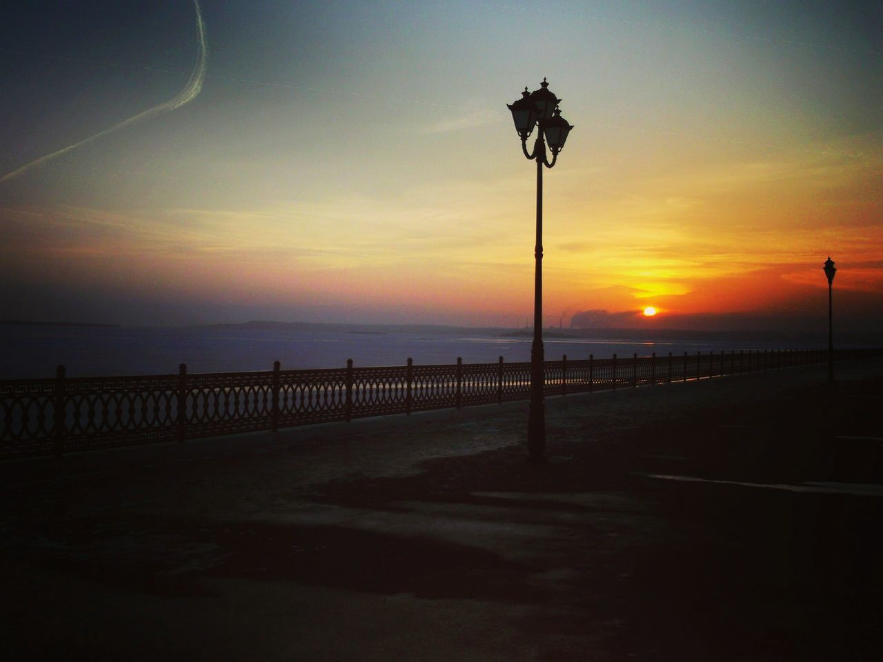 sunset, silhouette, sea, nature, scenics, beauty in nature, tranquil scene, tranquility, sky, street light, outdoors, no people, beach, horizon over water, water