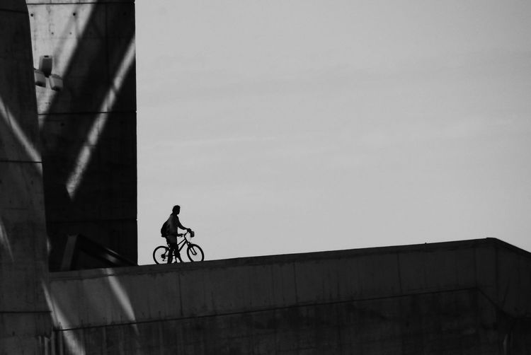 Man riding bicycle against sky
