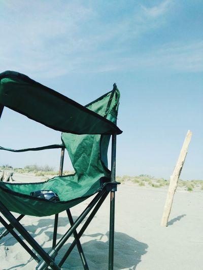 Empty chair on beach against sky