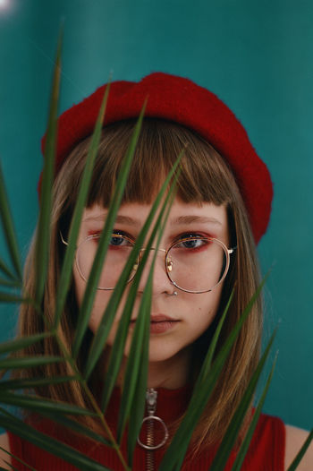 Close-up portrait of teenage girl wearing eyeglasses with plant standing against wall