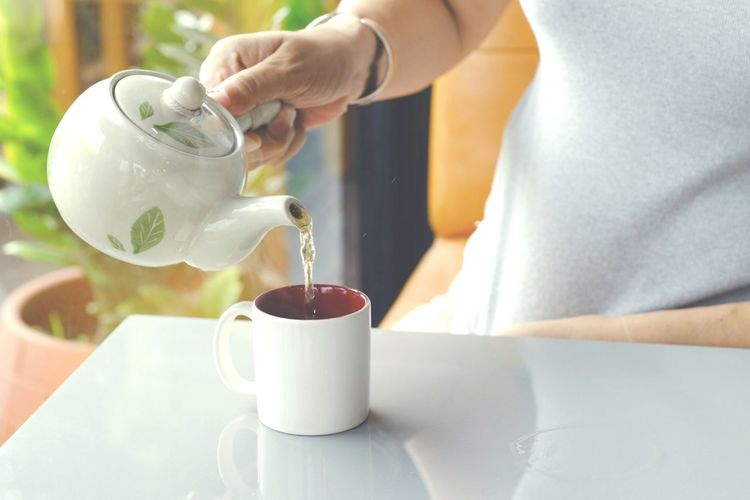 A woman's hand is pouring hot tea from a teapot into a white ceramic glass. Afternoon Tea Aroma ASIA Asian  Background Thailand Taste Beverage Caffeine Casual Closeup Cozy Delicious Easy Familiar Lifestyle Refreshment Tasty Hot Food Fresh Cafeteria Coffeeshop Comfortable Eat Drink Tea - Hot Drink Motion Holding Women Filling Tea Cup Herbal Tea