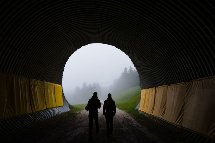 Rear View Of Silhouette People Walking In Tunnel During Foggy Weather