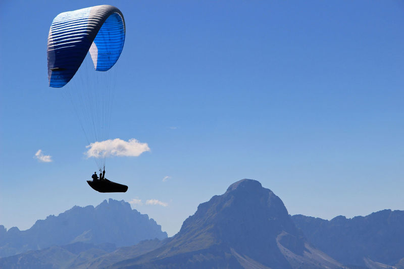 Paraglide flying at dolomites mountains against blue sky
