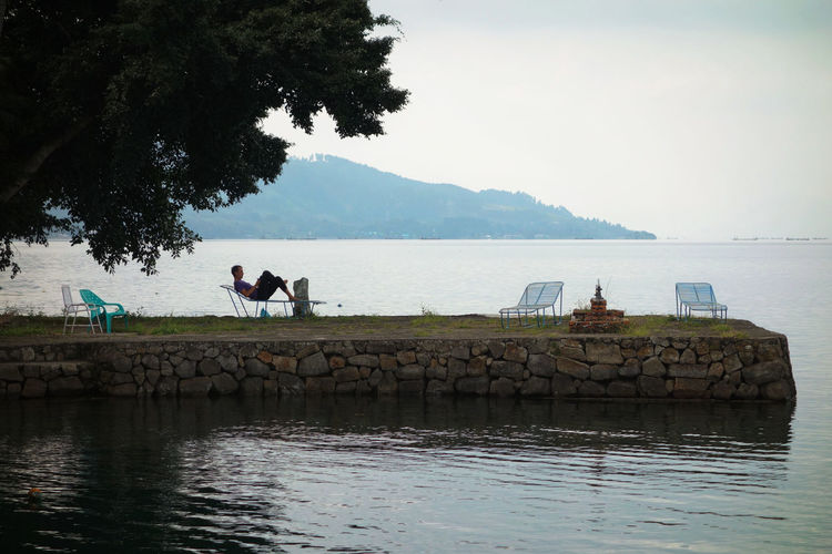 Sumatra  Toba Lake Architecture Beauty In Nature Clear Sky Day Full Length Leisure Activity Lifestyles Men Mountain Nature Outdoors People Real People Scenics Sea Sky Standing Tree Two People Water Women