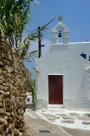 street view of Chora with white church with bell tower near a stone wall with bamboo plant Architecture Built Structure Place Of Worship Building Exterior Building Religion Spirituality Belief Nature Day No People Sunlight Whitewashed Sky Plant Bell Tower - Tower Low Angle View Outdoors Stone Wall Mykonos,Greece Bamboo - Plant Street Street View Greek Greek Architecture Urban Church White Building