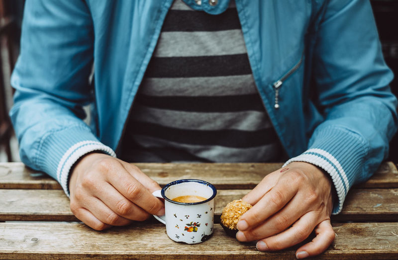 Midsection of man holding coffee cup on table