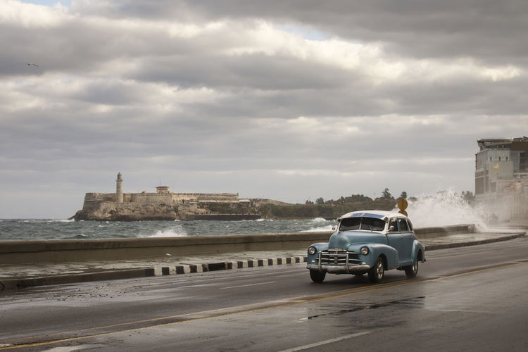 View of car on sea against cloudy sky