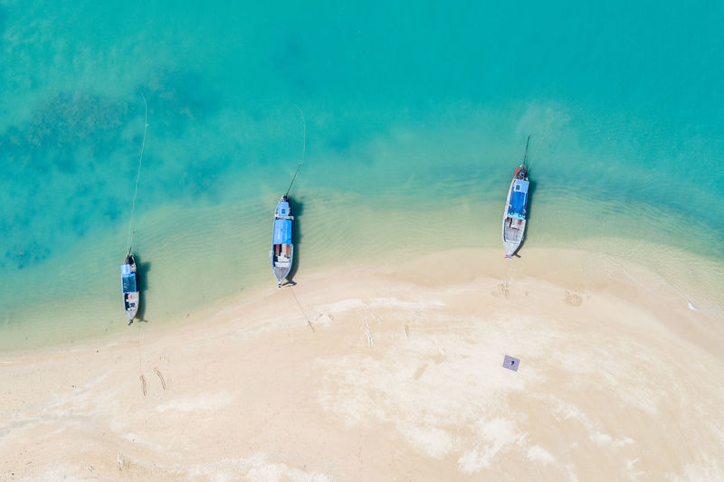 Three long tail boat on the beach in thailand aerial view