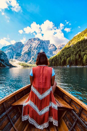 Rear View Of Woman Sitting On Canoe Against Mountains