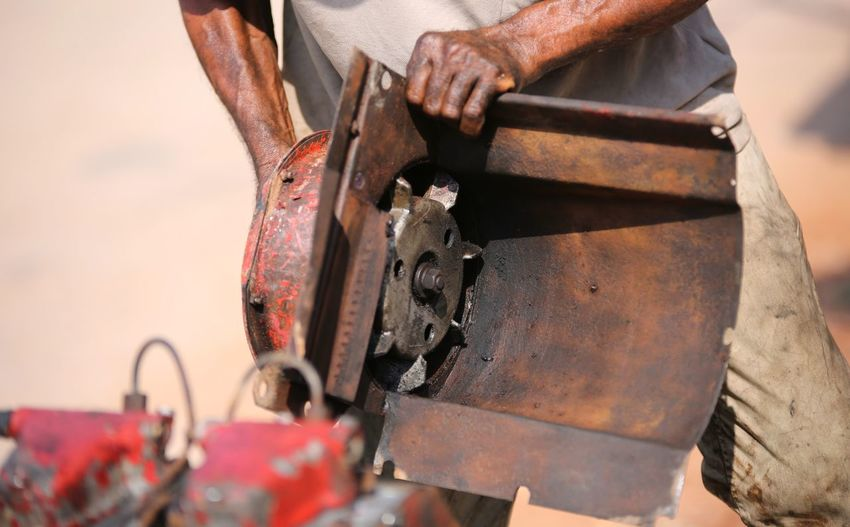 Midsection of man working on rusty machinery