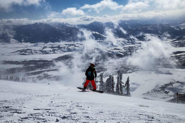 Man snowboarding on mountain against sky